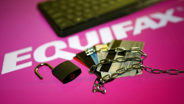 Credit cards, a chain and an open padlock is seen in front of displayed Equifax logo in this illustration taken September 8, 2017 - Sputnik International