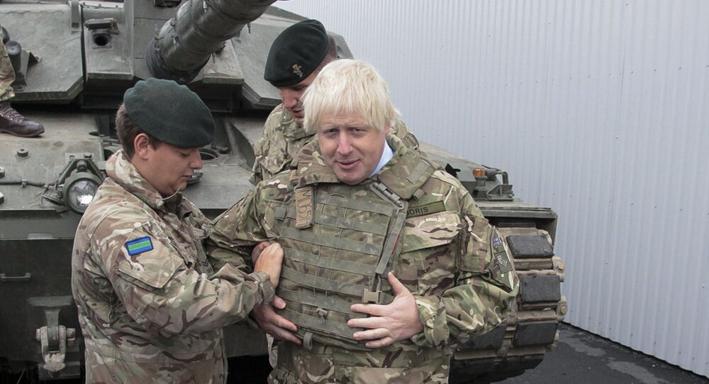 British Foreign Secretary Boris Johnson, right, has a flack jacket adjusted by an unidentified serviceman while visiting a NATO military unit outside Tallinn, Estoni