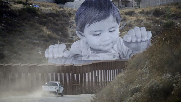 A Border Patrol vehicle drives in front of a mural in Tecate, Mexico, just beyond a border structure Friday, Sept. 8, 2017, in Tecate, Calif. - Sputnik International