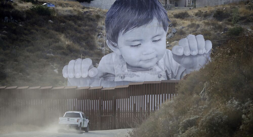 A Border Patrol vehicle drives in front of a mural in Tecate, Mexico, just beyond a border structure Friday, Sept. 8, 2017, in Tecate, Calif.