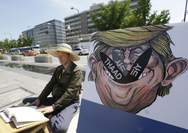 A South Korean protester sits next to a poster with an illustration of U.S. President Donald Trump to oppose a plan to deploy an advanced U.S. missile defense system called Terminal High-Altitude Area Defense, or THAAD, near the U.S. Embassy in Seoul Monday, June 5, 2017