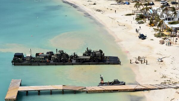 In this undated photo provided by the Ministry of Defence on Friday, Sept. 8, 2017, taken from a Royal Navy helicopter, a RLC Mexeflote approaches Sandy Bay Village beach, in Anguilla loaded with the 2 JCBs, 1 flatbed lorry, fork lift truck, BV 206 multi terrain vehicle, a Land Rover and a mobile generator. - Sputnik International