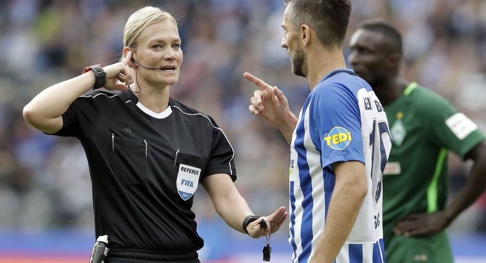 Referee Bibiana Steinhaus, left, speaks to a player during the German Bundesliga soccer match between Hertha BSC Berlin and SV Werder Bremen in Berlin, Germany, Sunday, Sept. 10, 2017.
