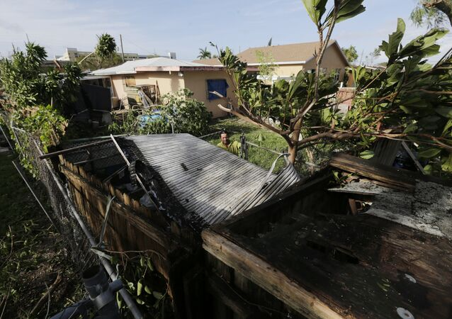 Bayardo Perez prepares to dismantle the mangled tin roof of his shed in Sweetwater, Fla., Monday, Sept. 11.