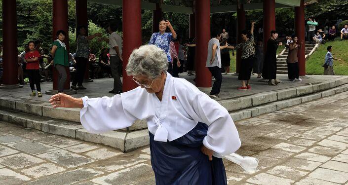Elderly woman dances on the street in Pyongyang