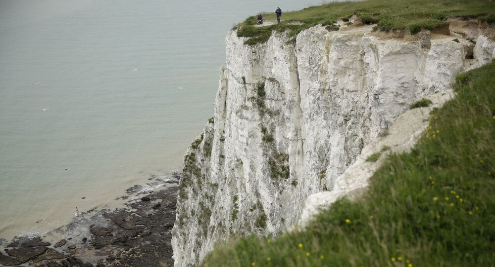 Visitors look down from the top of a section of the White Cliffs of Dover, south east England, Thursday, June 9, 2016.