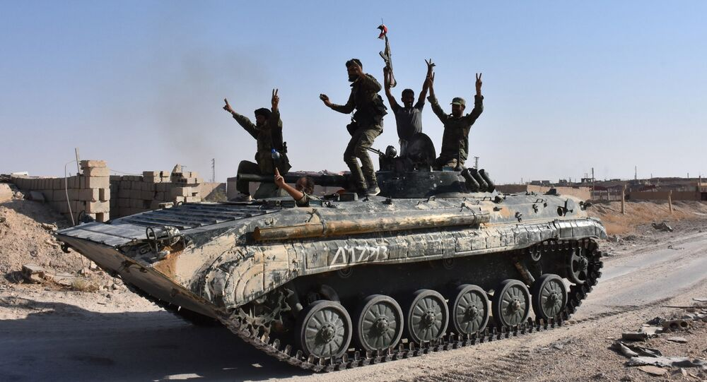 Syrian government forces celebrate in the eastern Syrian city of Deir Ezzor on September 11, 2017 as they continue to press forward with Russian air cover in the offensive against Islamic State group jihadists across the province