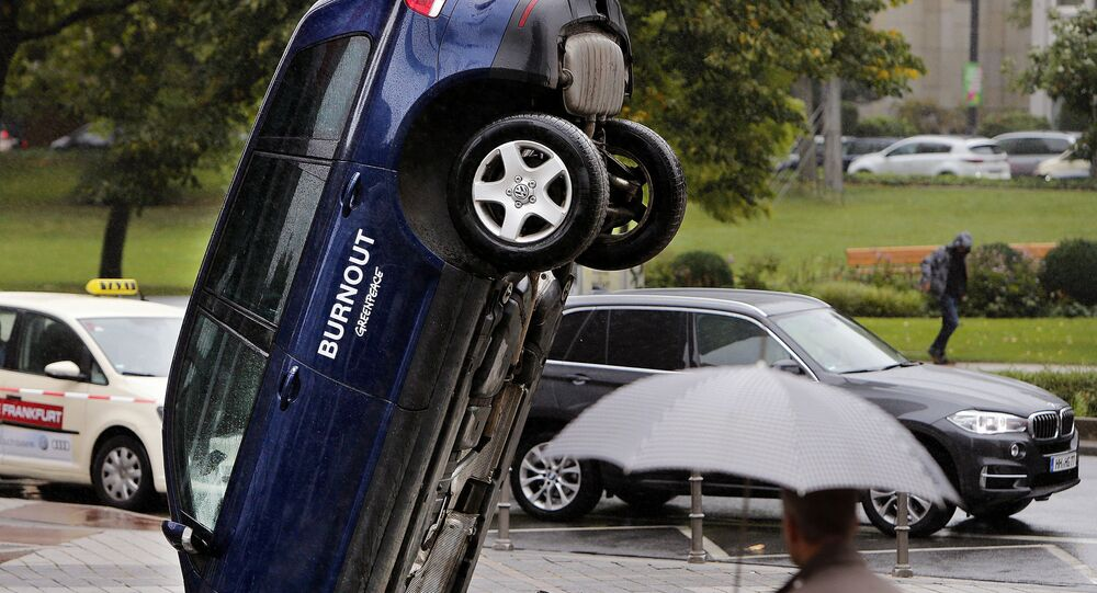 A Volkswagen Touareg stands upside down in front of the fair ground of the IAA Motor Show in Frankfurt, Germany, Wednesday, Sept. 13, 2017. The environmental organization Greenpeace installed the car the day before to protest against the car industry. From frighteningly fast hypercars to new electric SUVs, the Frankfurt auto show is a major event for car lovers wanting to get a glimpse of the future.