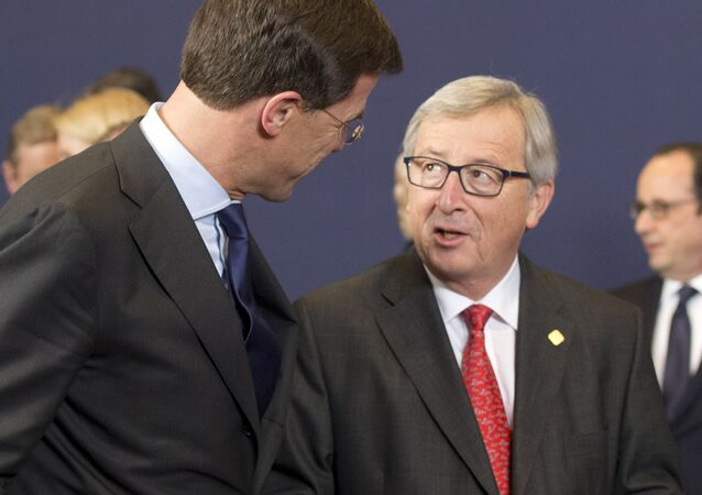 European Commission President Jean-Claude Juncker, center right, speaks with Dutch Prime Minister Mark Rutte during a group photo at an EU summit in Brussels on Thursday, Feb. 12, 2015.