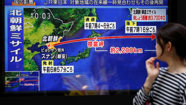 A passerby looks at a TV screen reporting news about North Korea's missile launch in Tokyo, Japan September 15, 2017 - Sputnik International