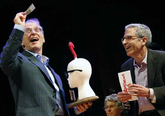 James Heathcote, left, reacts after receiving the Ig Nobel Anatomy Prize from Nobel laureate Eric Maskin (economics, 2007) during ceremonies at Harvard University in Cambridge, Mass