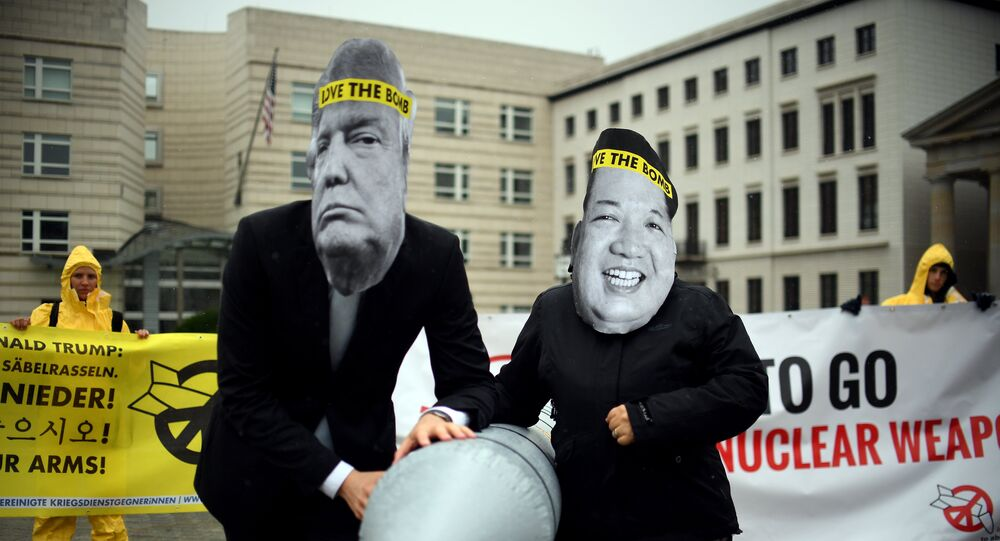 Activists of the non-governmental organization International Campaign to Abolish Nuclear Weapons (ICAN) wear masks of US President Donal Trump and leader of the Democratic People's Republic of Korea Kim Jon-un while posing with a mock missile in front of the embassy of Democratic People's Republic of Korea in Berlin, on September 13, 2017