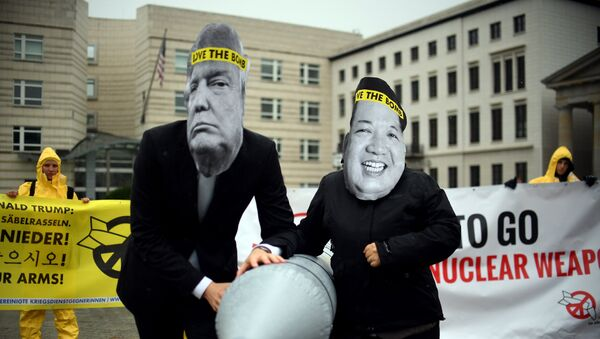 Activists of the non-governmental organization International Campaign to Abolish Nuclear Weapons (ICAN) wear masks of US President Donal Trump and leader of the Democratic People's Republic of Korea Kim Jon-un while posing with a mock missile in front of the embassy of Democratic People's Republic of Korea in Berlin, on September 13, 2017 - Sputnik International