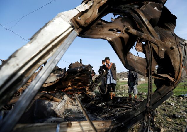 People look at the wreckage of a taxi car destroyed by a Saudi-led air strike on a checkpoint of the armed Houthi movement near Sanaa, Yemen August 30, 2017