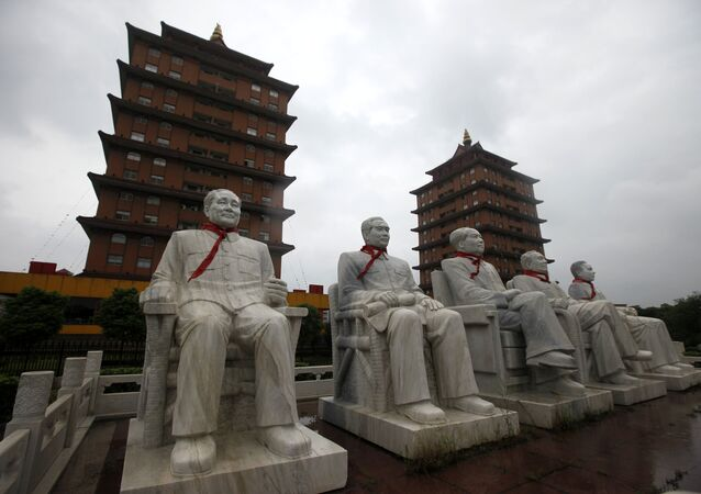 This Aug. 10, 2009 photo shows statues of Deng Xiaoping, Zhou Enlai, Mao Zedong, Zhu De and Liu Shaoqi in front of traditional pagoda-like buildings at Happiness Garden Monday in Huaxi, Jiangsu Province, China