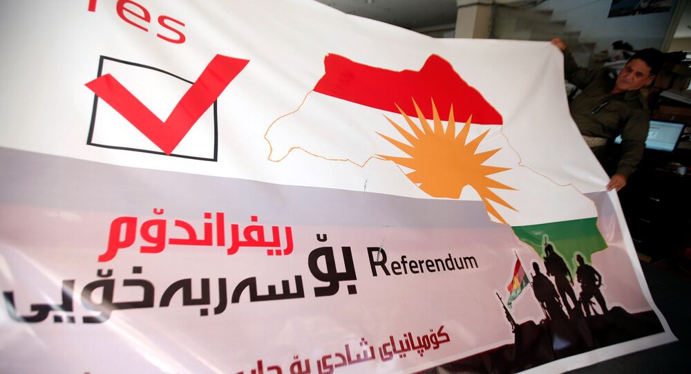 A man holds a printed banner of Kurdistan region referendum in Erbil, Iraq August 26, 2017. Picture taken August 26, 2017