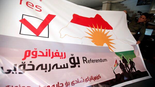 A man holds a printed banner of Kurdistan region referendum in Erbil, Iraq August 26, 2017. Picture taken August 26, 2017 - Sputnik International