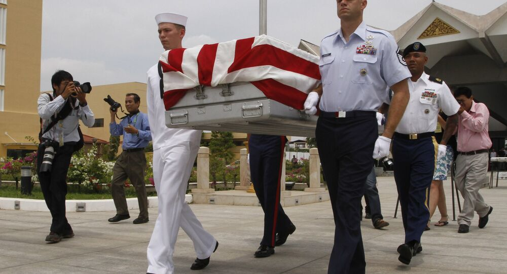 Four U.S. servicemen carry a coffin containing possible remains of a U.S. serviceman to a C-17 cargo plane during a repatriation ceremony at Phnom Penh International Airport, Cambodia, Wednesday, April 2, 2014.