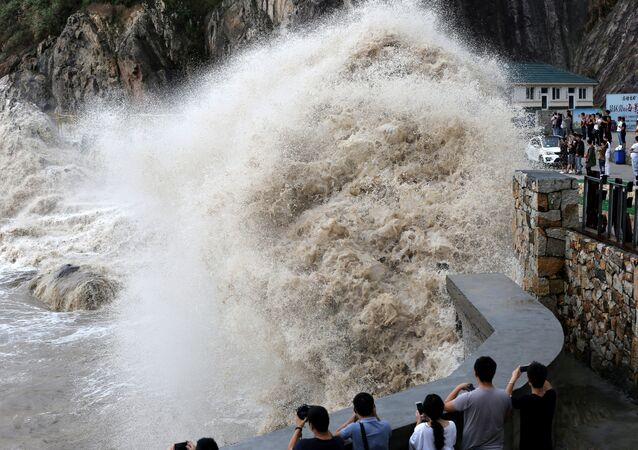 People stand beside a big wave on a waterfront as Typhoon Talim approaches in Wenling, Zhejiang province, China September 14, 2017