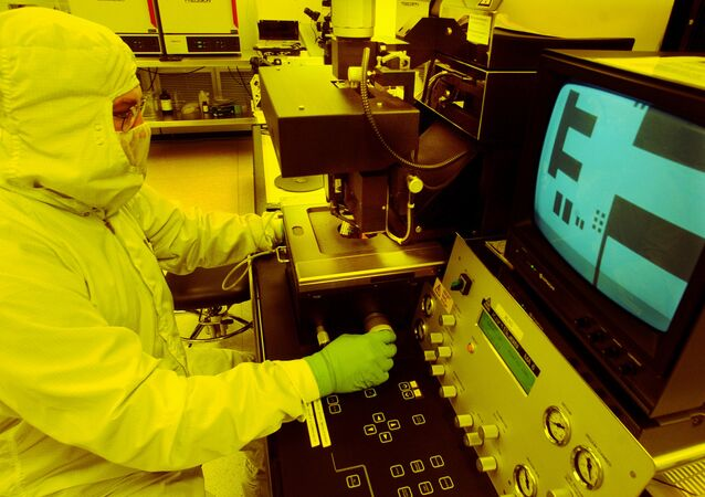 A microchip is projected on a screen by a microscope in a photo lithography room where film emulsion is applied to a microchip wafer