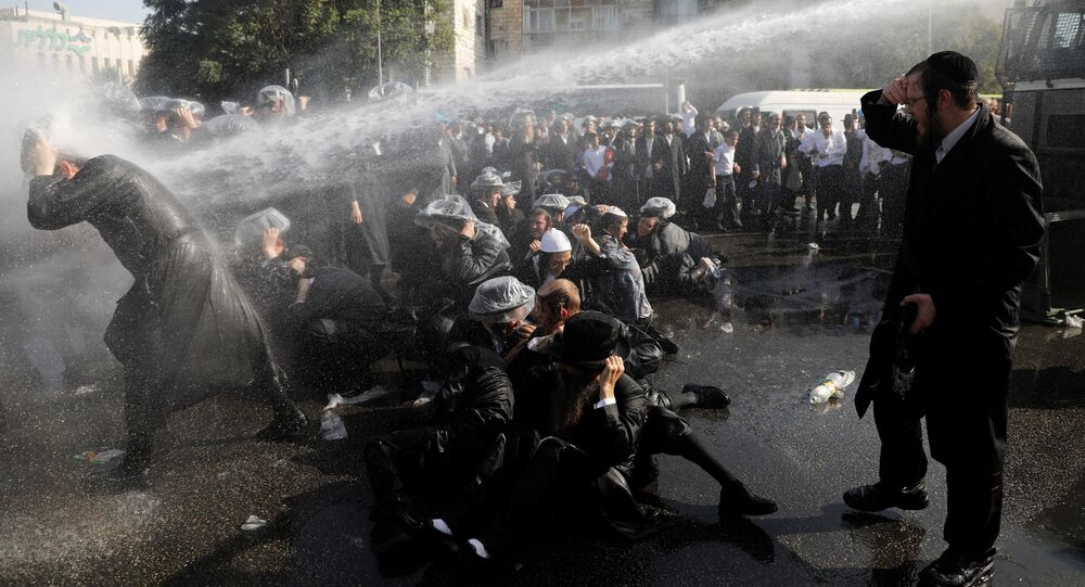 Israeli ultra-Orthodox Jewish men are sprayed with water during clashes with police at a protest against the detention of a member of their community who refuses to serve in the Israeli army, in Jerusalem September 17, 2017