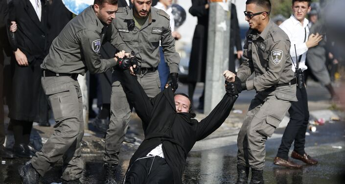 Members of the Israeli security forces drag an ultra-Orthodox Jewish demonstrator in an ultra-Orthodox neighbourhood of Jerusalem on September 17, 2017 during a protest against a court ruling that could require them to serve in the army like their secular counterparts