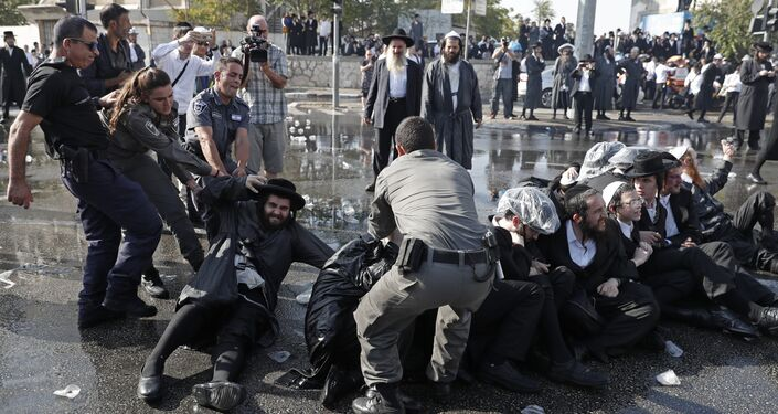 Israeli security forces remove Ultra-Orthodox Jewish demonstrators from the road in an ultra-Orthodox neighbourhood of Jerusalem on September 17, 2017 as they protest against a court ruling that could require them to serve in the army like their secular counterparts