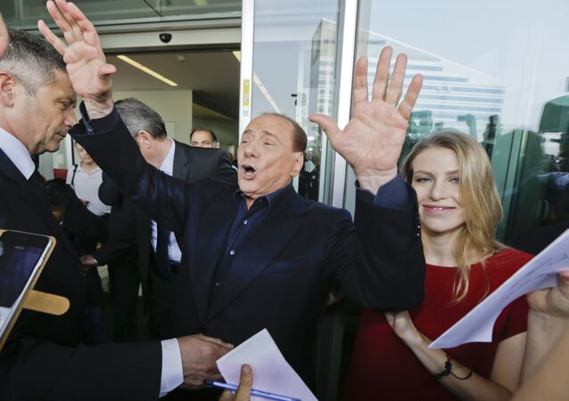 In this file photo taken on July 3, 2015, AC Milan president Silvio Berlusconi waves to supporters flanked by his daughter Barbara, outside the Milanese soccer club's headquarters, in Milan, Italy.