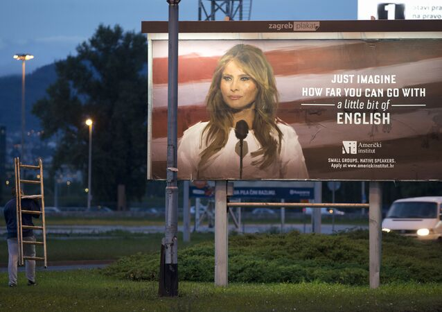 A worker carrying a ladder walks past a billboard depicting the first lady Melania Trump and advertising a language school displayed in Zagreb, Croatia, Friday, Sept. 15, 2017.