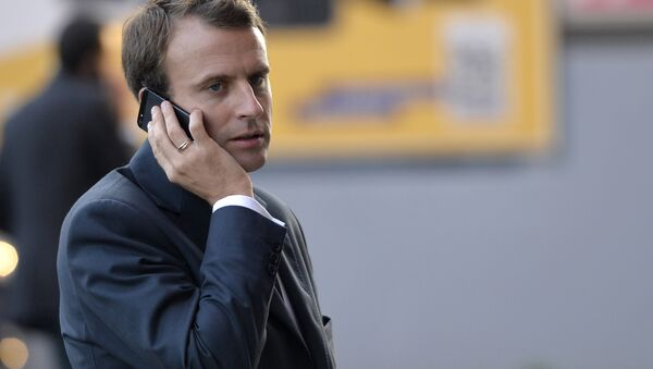 French Economy and Industry minister Emmanuel Macron gives a phone as he visits the 2014 Paris Auto Show on October 3, 2014 in Paris on the second of the two press days. - Sputnik International