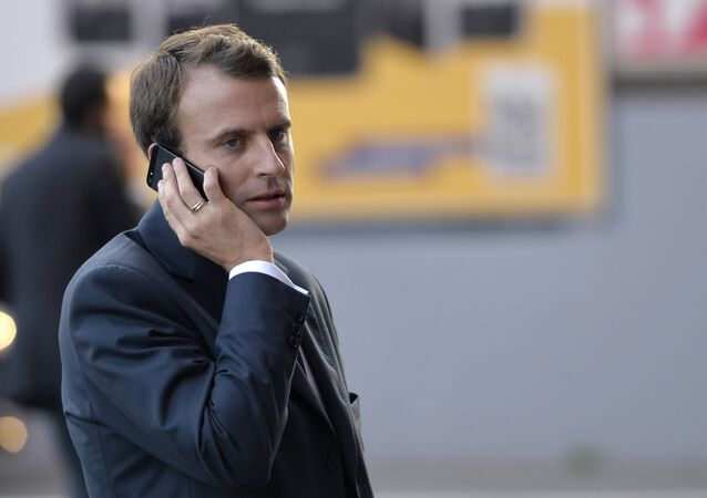 French Economy and Industry minister Emmanuel Macron gives a phone as he visits the 2014 Paris Auto Show on October 3, 2014 in Paris on the second of the two press days.