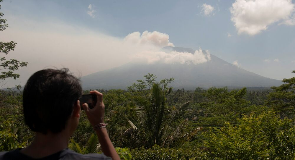 A local resident takes a picture of Mount Agung, an active volcano that authorities say is showing increased activity, from a monitoring station in Rendang Village, Karangasem on the resort island of Bali, Indonesia September 19, 2017