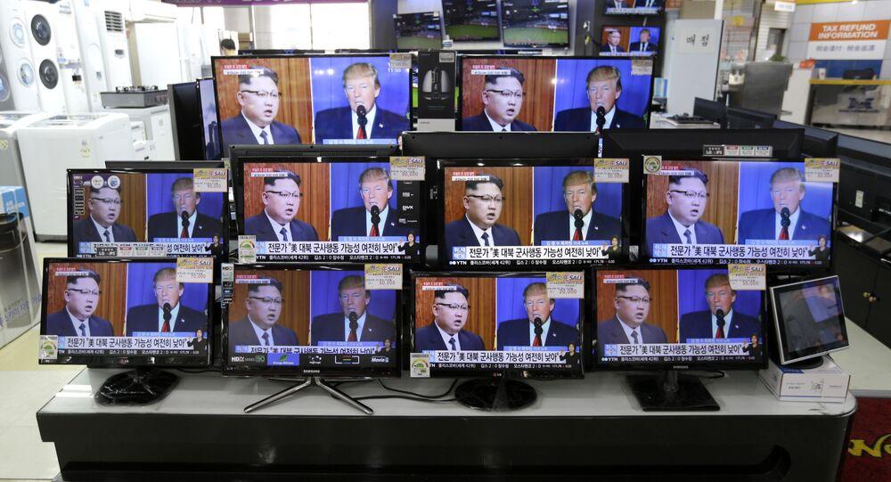 TV screens show a news program with an image of U.S. President Donald Trump and North Korean leader Kim Jong Un