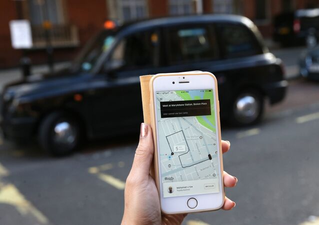 A woman poses holding a smartphone showing the App for ride-sharing cab service Uber in London on September 22, 2017