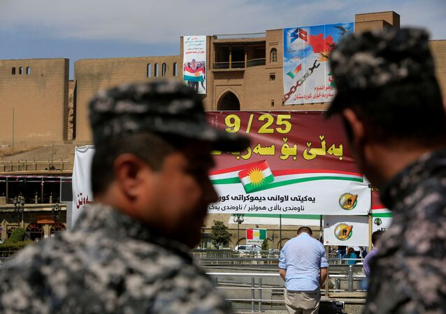 Kurdish policemen look on towards banners supporting the referendum for independence of Kurdistan in Erbil, Iraq September 24, 2017