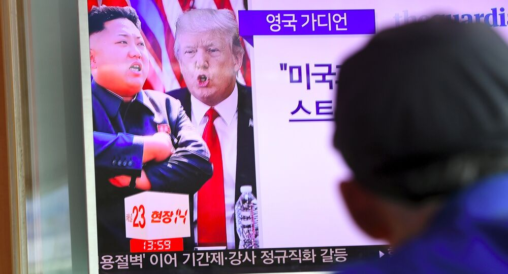 A man watches a television news programme showing US President Donald Trump (C) and North Korean leader Kim Jong-Un (L) at a railway station in Seoul on August 9, 2017