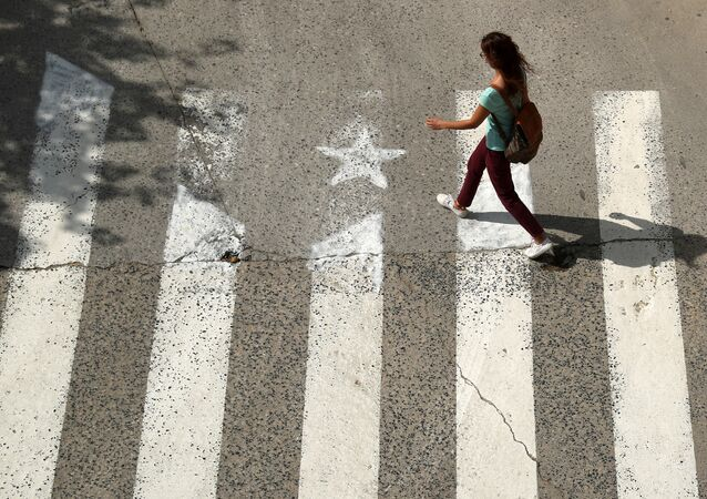 A woman walks past a crosswalk, painted in the form of an Estelada (Catalan pro-independence flag) in Arenys de Munt, north of Barcelona, Spain, September 26, 2017