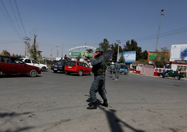 Afghan policemen stand guard outside of Kabul Airport after rockets exploded in Kabul, Afghanistan
