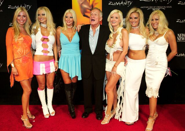 Playboy magazine founder Hugh Hefner poses with his six girlfriends