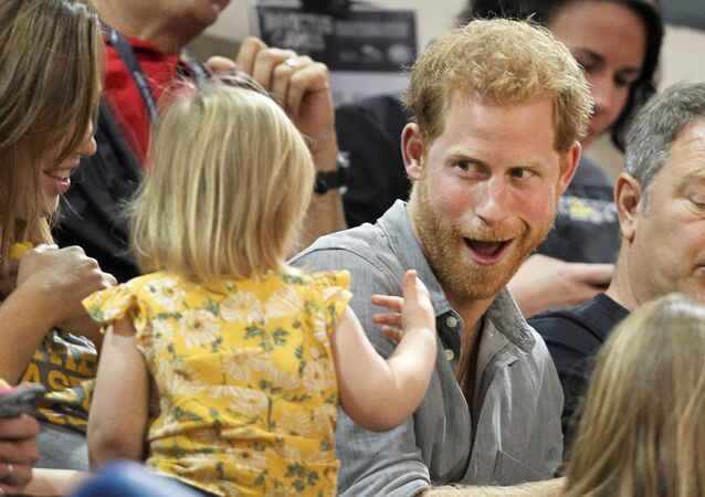 Britain's Prince Harry, patron of the Invictus Games Foundation, shares popcorn with a child while attending the Sitting Volleyball competition at the games in Toronto, Ontario, Canada, September 27, 2017.