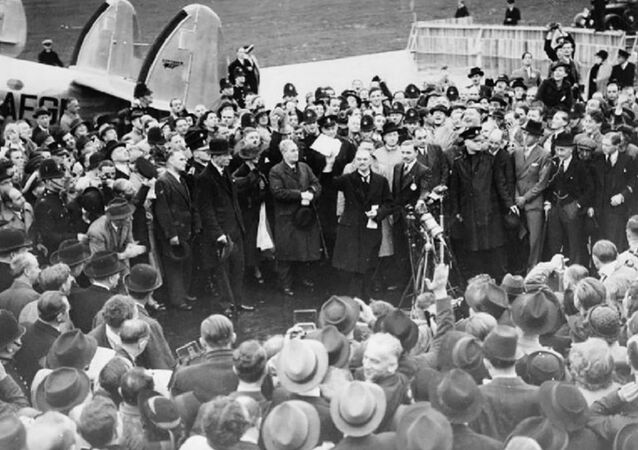 Neville Chamberlain holding the paper containing the resolution to commit to peaceful methods signed by both Hitler and himself on his return from Munich. He is showing the piece of paper to a crowd at Heston Aerodrome on 30 September 1938