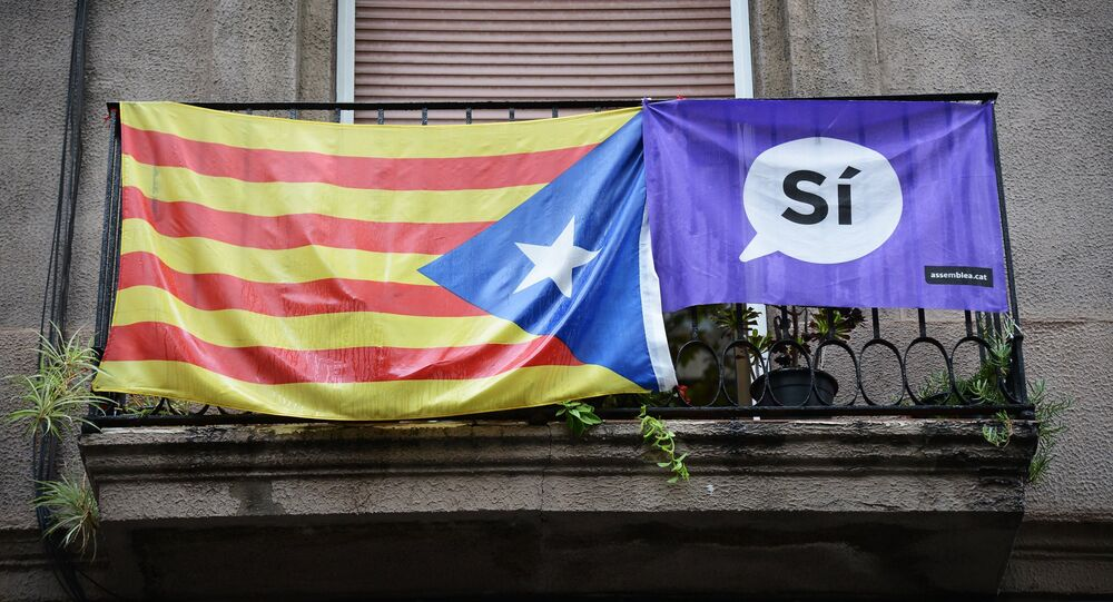 A campaign banner and a flag displayed on a balcony in Barcelona during Catalan independence referendum.
