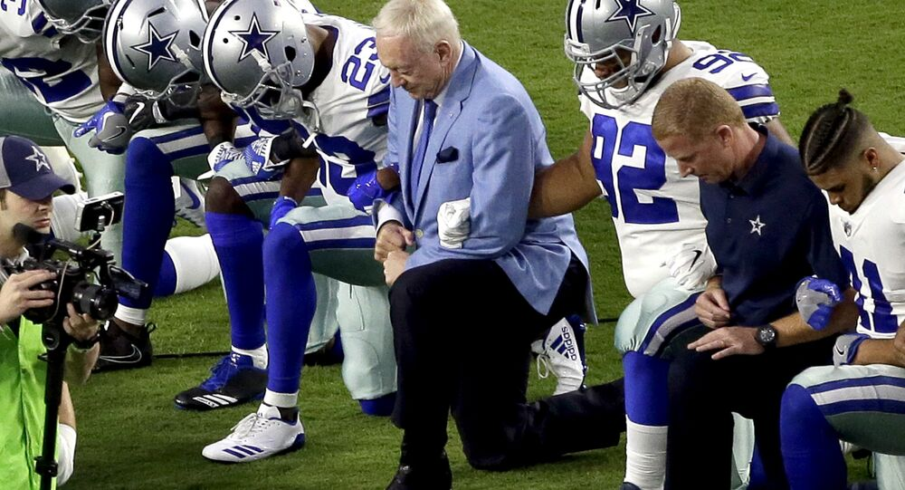 In this Monday, Sept. 25, 2017, file photo, the Dallas Cowboys, led by owner Jerry Jones, center, take a knee prior to the national anthem before an NFL football game against the Arizona Cardinals in Glendale, Ariz. What began more than a year ago with a lone NFL quarterback protesting police brutality against minorities by kneeling silently during the national anthem before games has grown into a roar with hundreds of players sitting, kneeling, locking arms or remaining in locker rooms, their reasons for demonstrating as varied as their methods.