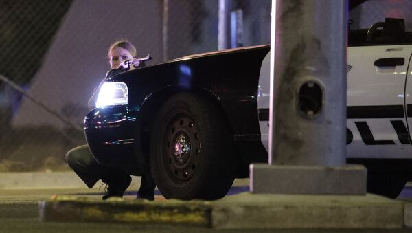 A police officer takes cover behind a police vehicle during a shooting near the Mandalay Bay resort and casino on the Las Vegas Strip, Sunday, Oct. 1, 2017, in Las Vegas - Sputnik International