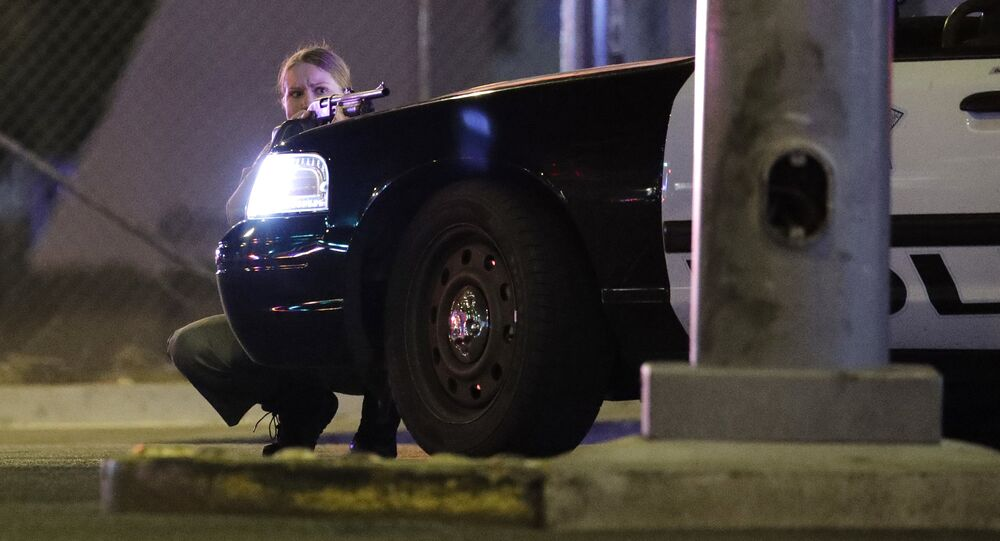 A police officer takes cover behind a police vehicle during a shooting near the Mandalay Bay resort and casino on the Las Vegas Strip, Sunday, Oct. 1, 2017, in Las Vegas