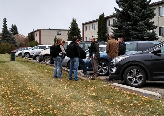 Plainclothes police gather outside an apartment building near downtown Edmonton, Alberta, Canada October 1, 2017 after a refugee was accused of stabbing an officer and running down four pedestrians in a car
