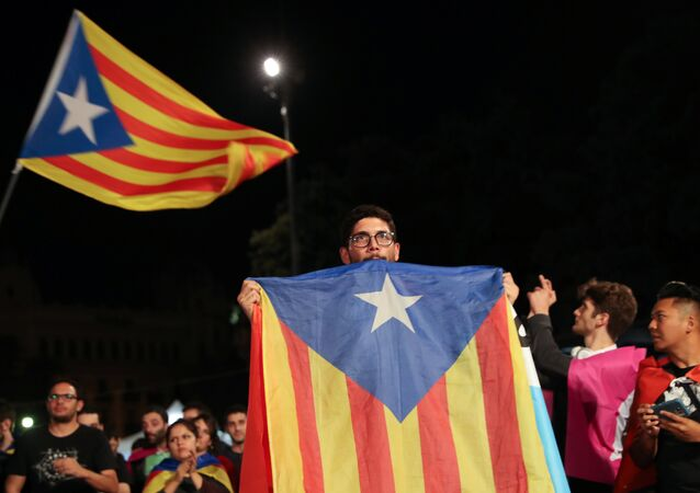 A man holds an Estelada (Catalan separatist flag) as people gather at Plaza Catalunya after voting ended for the banned independence referendum, in Barcelona, Spain