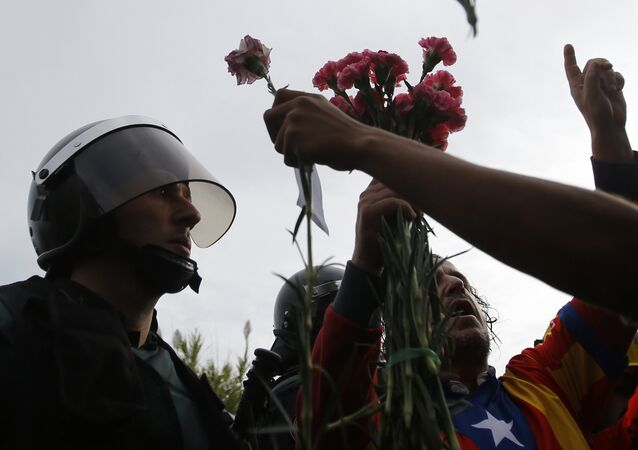 People try to offer flowers to a civil guard at the entrance of a sports center, assigned to be a referendum polling station by the Catalan government in Sant Julia de Ramis, near Girona, Spain, Sunday, Oct. 1, 2017. Scuffles have erupted as voters protested while dozens of anti-rioting police broke into a polling station where the regional leader was expected to show up for voting on Sunday.