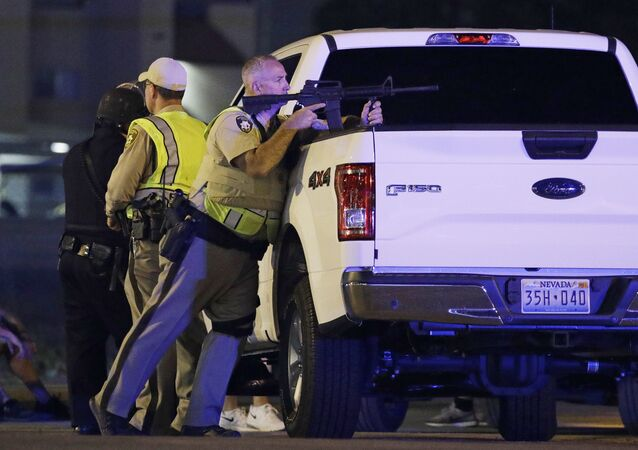 A police officer takes cover behind a truck at the scene of a shooting near the Mandalay Bay resort and casino on the Las Vegas Strip, Sunday, Oct. 1, 2017, in Las Vegas