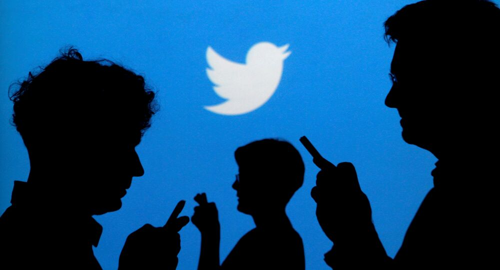 People holding mobile phones are silhouetted against a backdrop projected with the Twitter logo. (File)